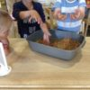 Code 497 Bright coloured rice in tray with 2 kids fingers